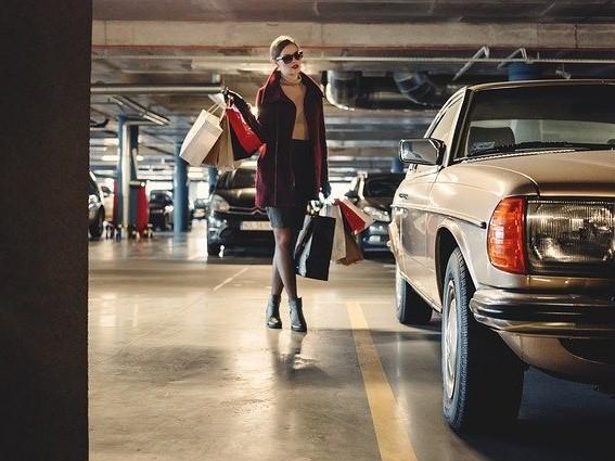 ショッピングバッグを持って車に乗り込もうとする女性