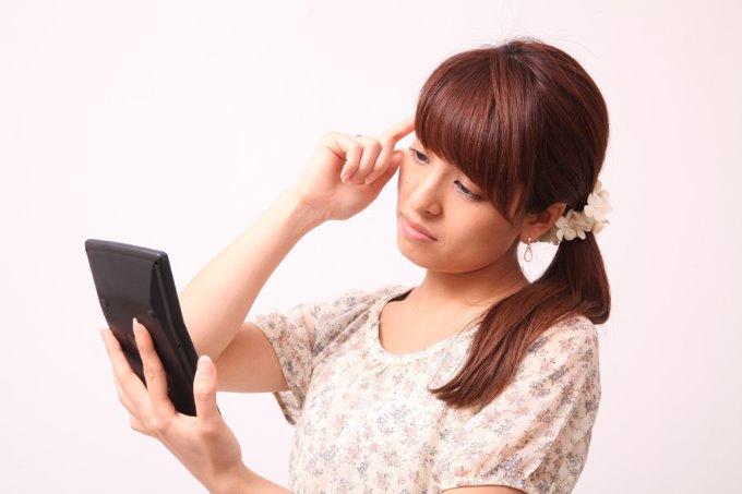 電卓を手に悩む女性