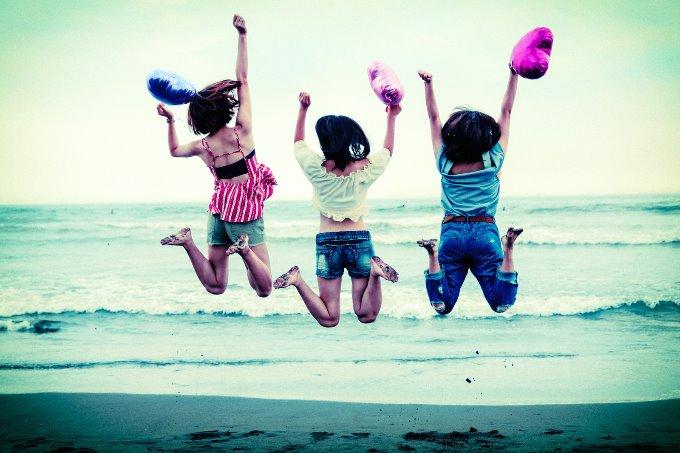 海辺でジャンプする三人の女性