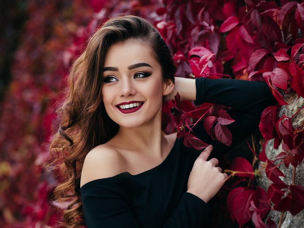 花の壁の前でほほ笑む少女