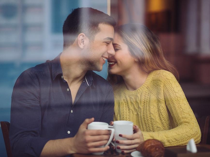 コーヒーショップの幸せな若いカップル