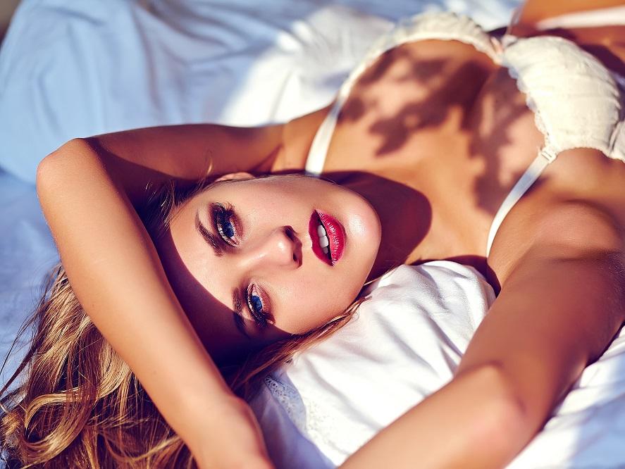 朝陽を浴びてベッドに横たわる美しい女性