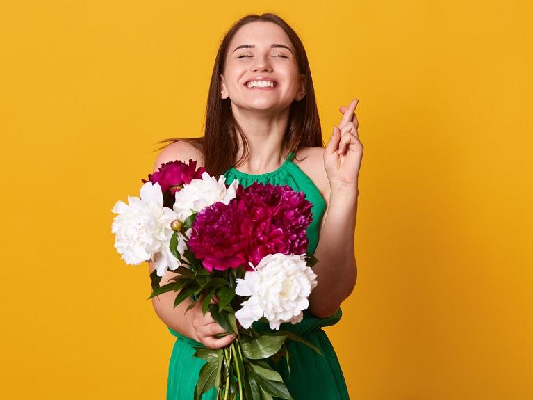 ボタンを抱えて喜びの表情を浮かべる女性