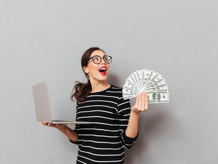 ノートパソコンと大金を手に喜ぶ女性