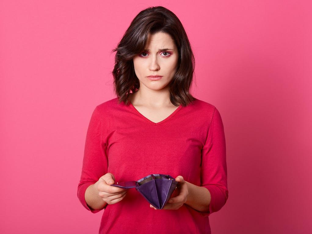 空の財布を持つ悲しい表情の女性