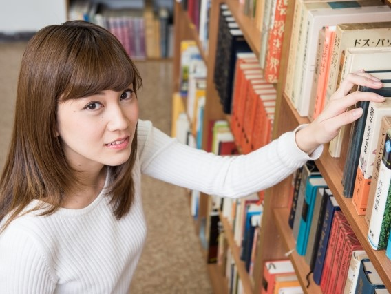 図書館の本棚から本を取り出す上目遣いの女子大学生