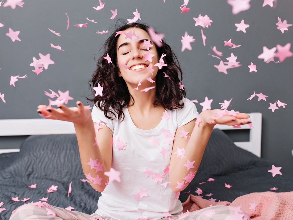 ベッドの上で紙の星をばらまく幸せそうな女性