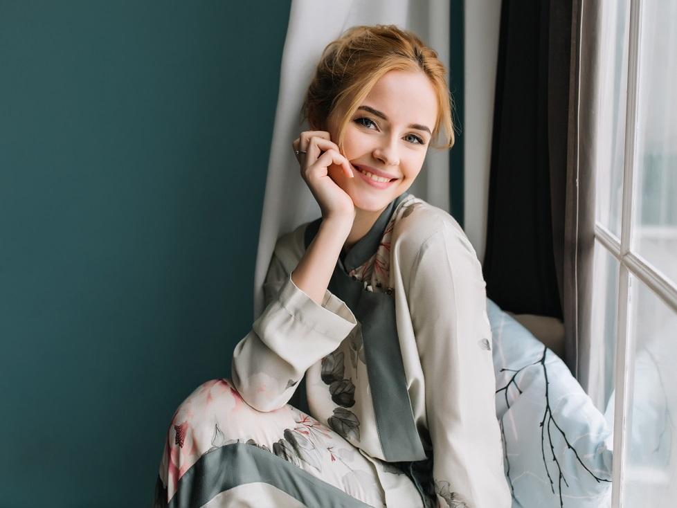 窓辺に座る笑顔の少女