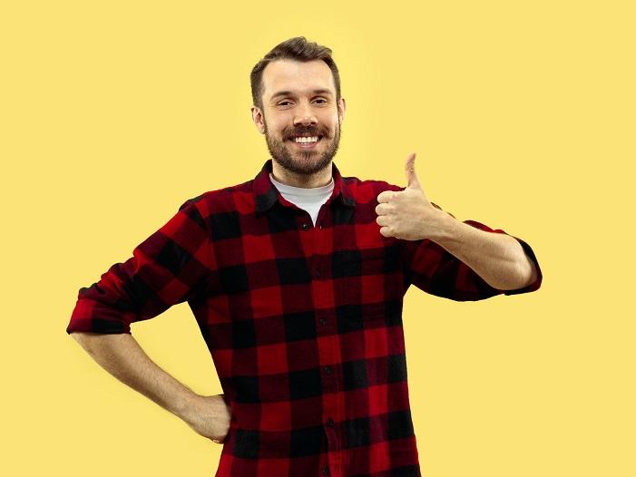 黄色の背面に赤いチェックシャツを着た若い男性