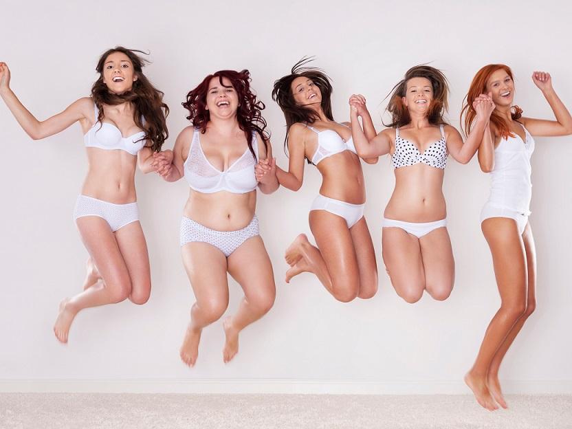 手をつないでジャンプする下着姿の若い5人の女性