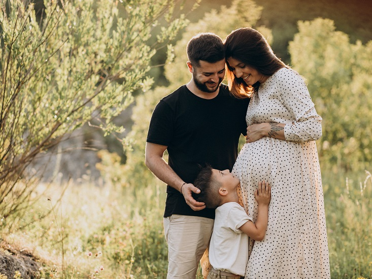 森林の中で夫と息子とほほ笑む若い妊娠中の女性
