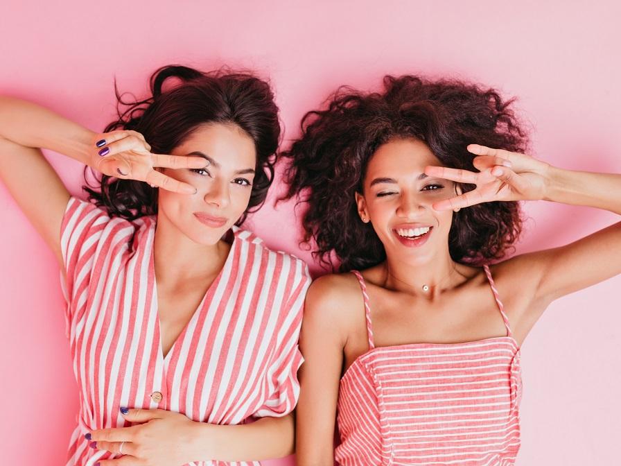 Vサインをするピンク色の服を着た二人の女性