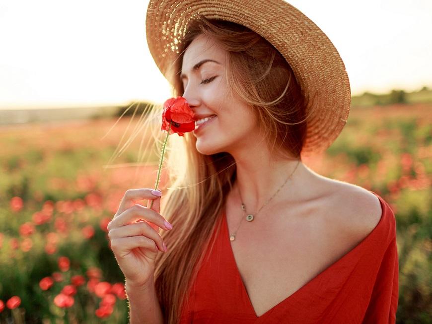 赤い花をもって香りを嗅ぐ麦わら帽子の女性