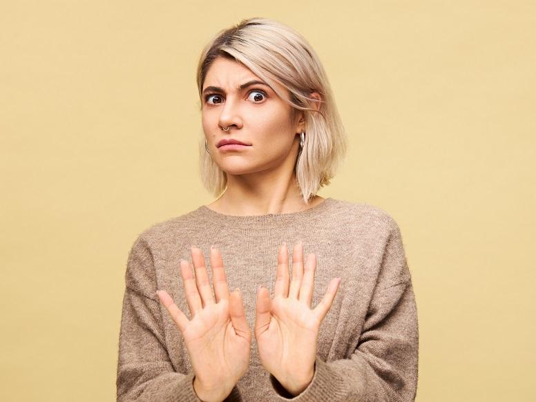 両手を体の正面に挙げて拒絶する金髪の女性