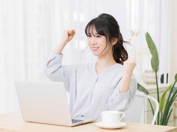パソコンの前で喜ぶ女性