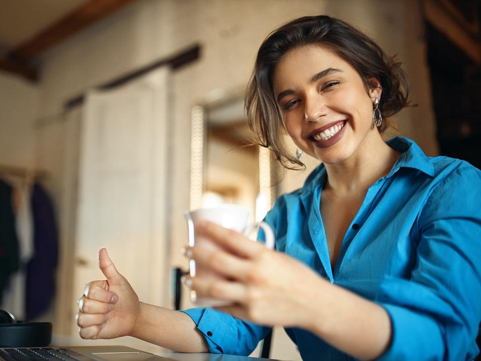 ネットをしながら微笑む青い服の女性