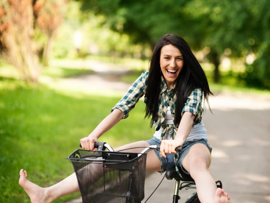 裸足で自転車を漕ぐ笑顔の自由な女性
