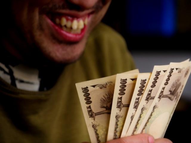 お金に笑う男性